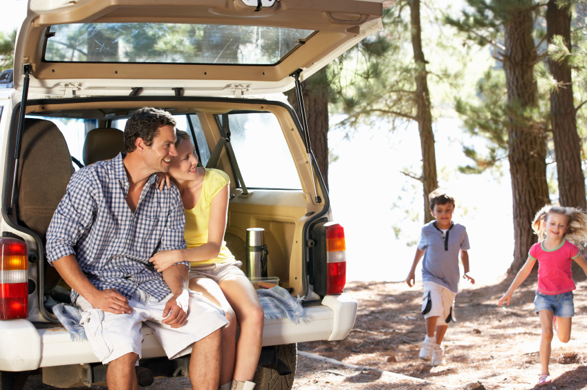 Young family on day out in country road trip car